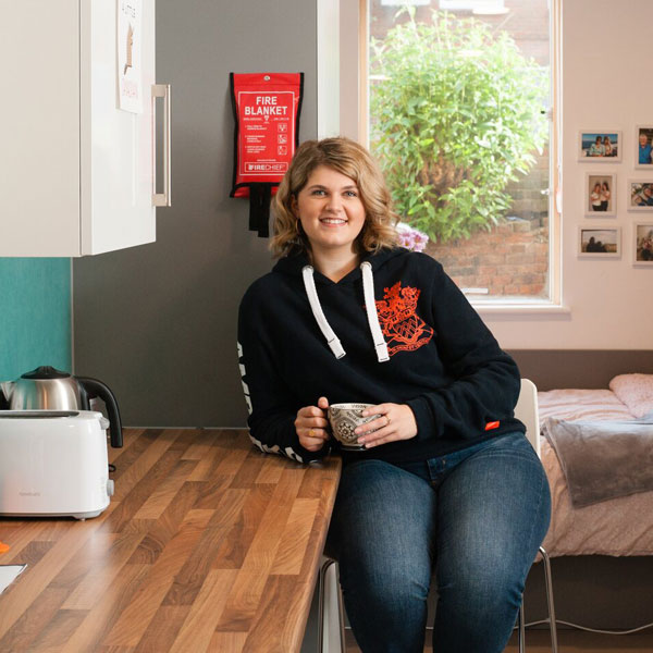 Student with cup of coffee sat in halls of residence studio