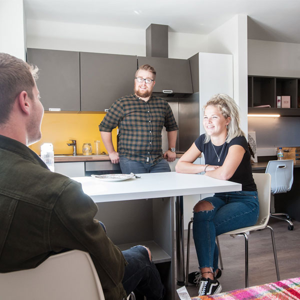 Students sat around kitchen table in halls of residence