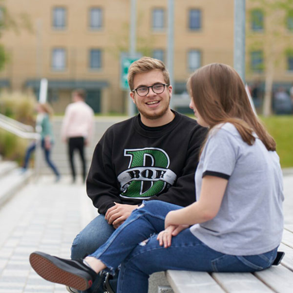 Students sat on bench at Pittville Student Village