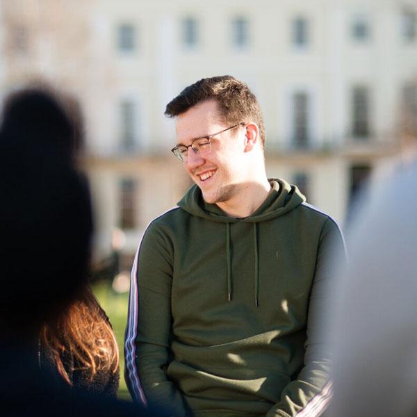 Student outside laughing in Montpellier Gardens, Cheltenham