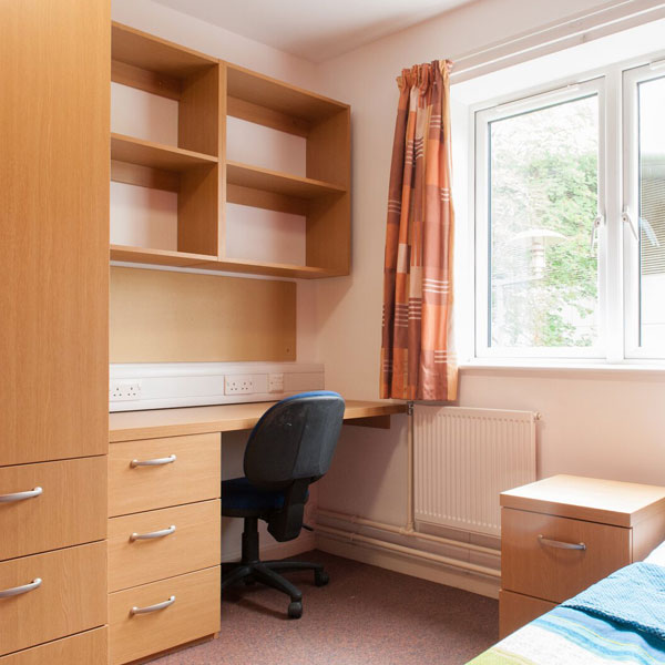 Halls of residence bedroom with chair, bed and desk