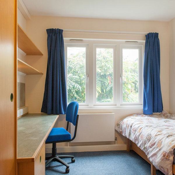 Halls of residence bedroom with bed and desk