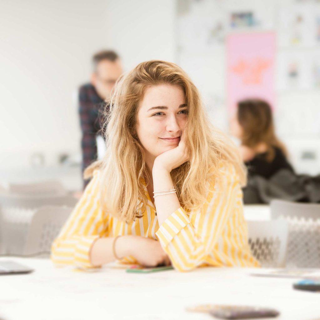 student smiling in graphic design studio