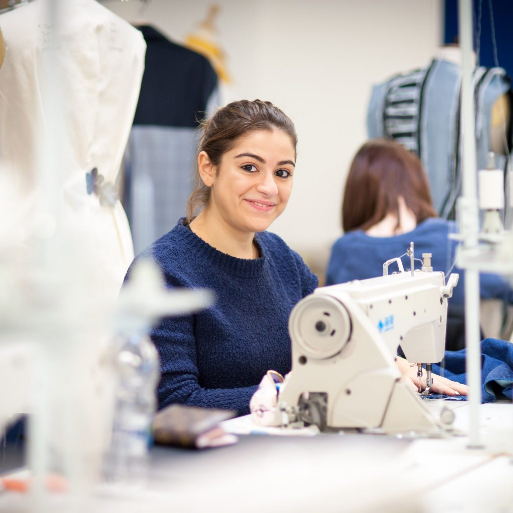 Student on Fashion Design course sitting at sewing machine at Hardwick