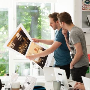 Two young men looking at advertising prints