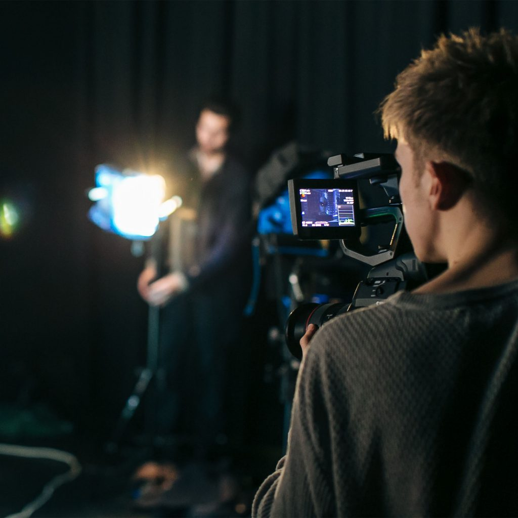 Students on Film and Television Production (Level 6) course looking through camera during practical in studio at Park campus