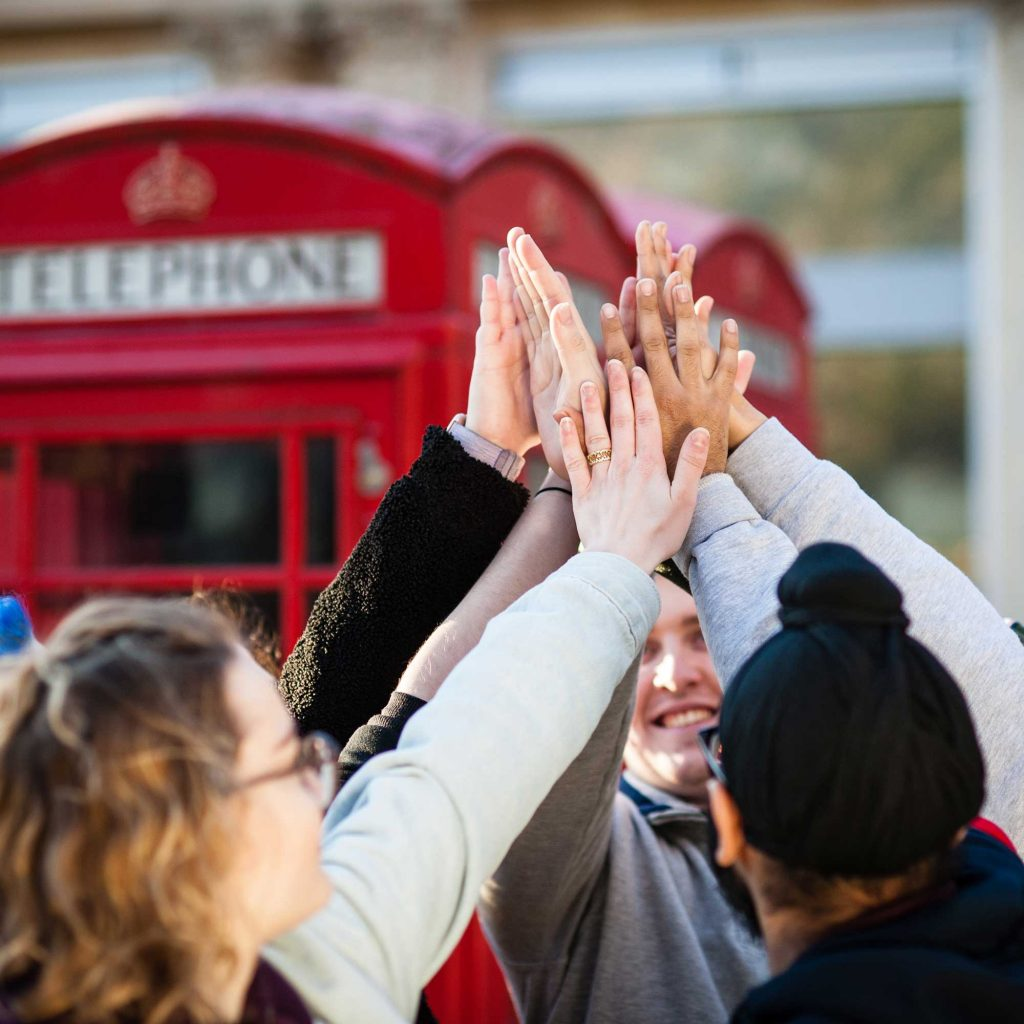 Students high-fiving in front of red telephone box