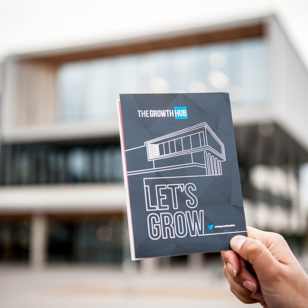Flyer for The Growth Hub with the University of Gloucestershire Business School in the BACKGROUND
