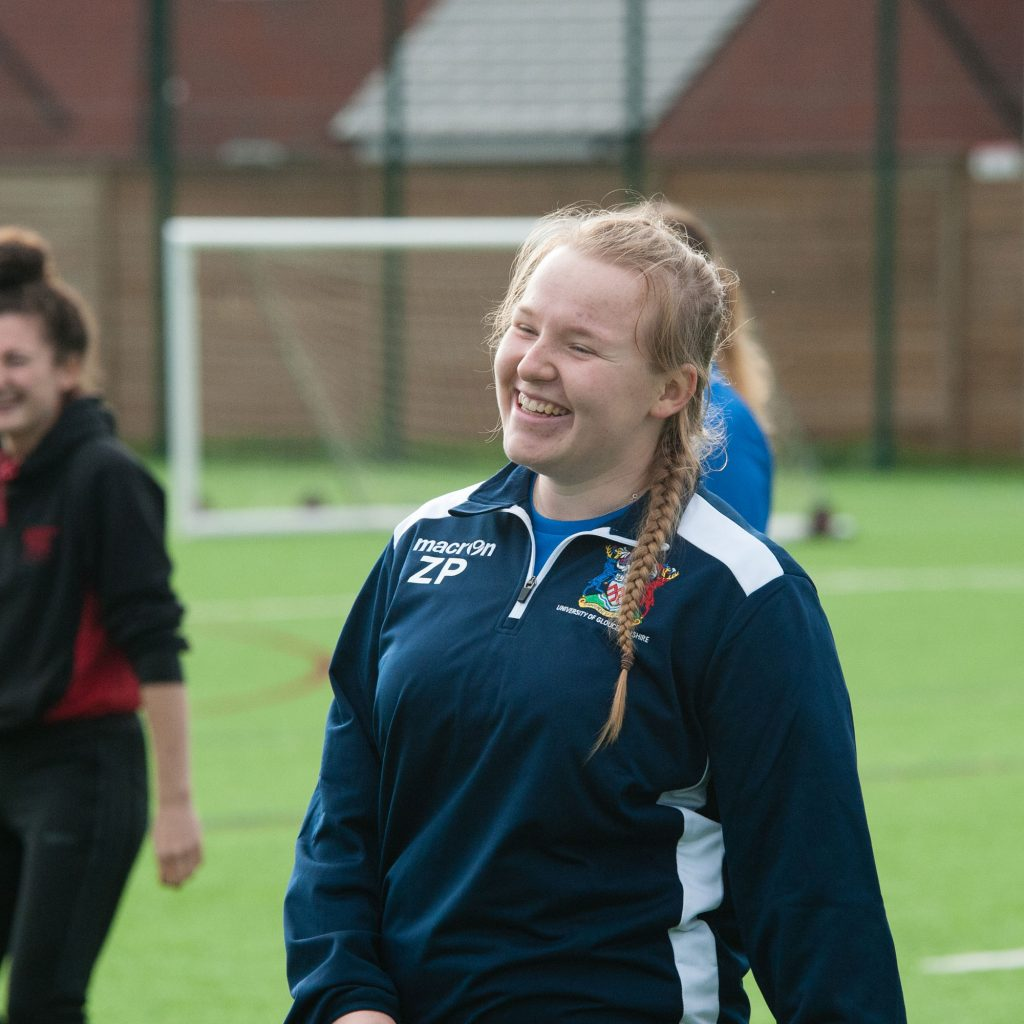 Student smiling on sports pitch