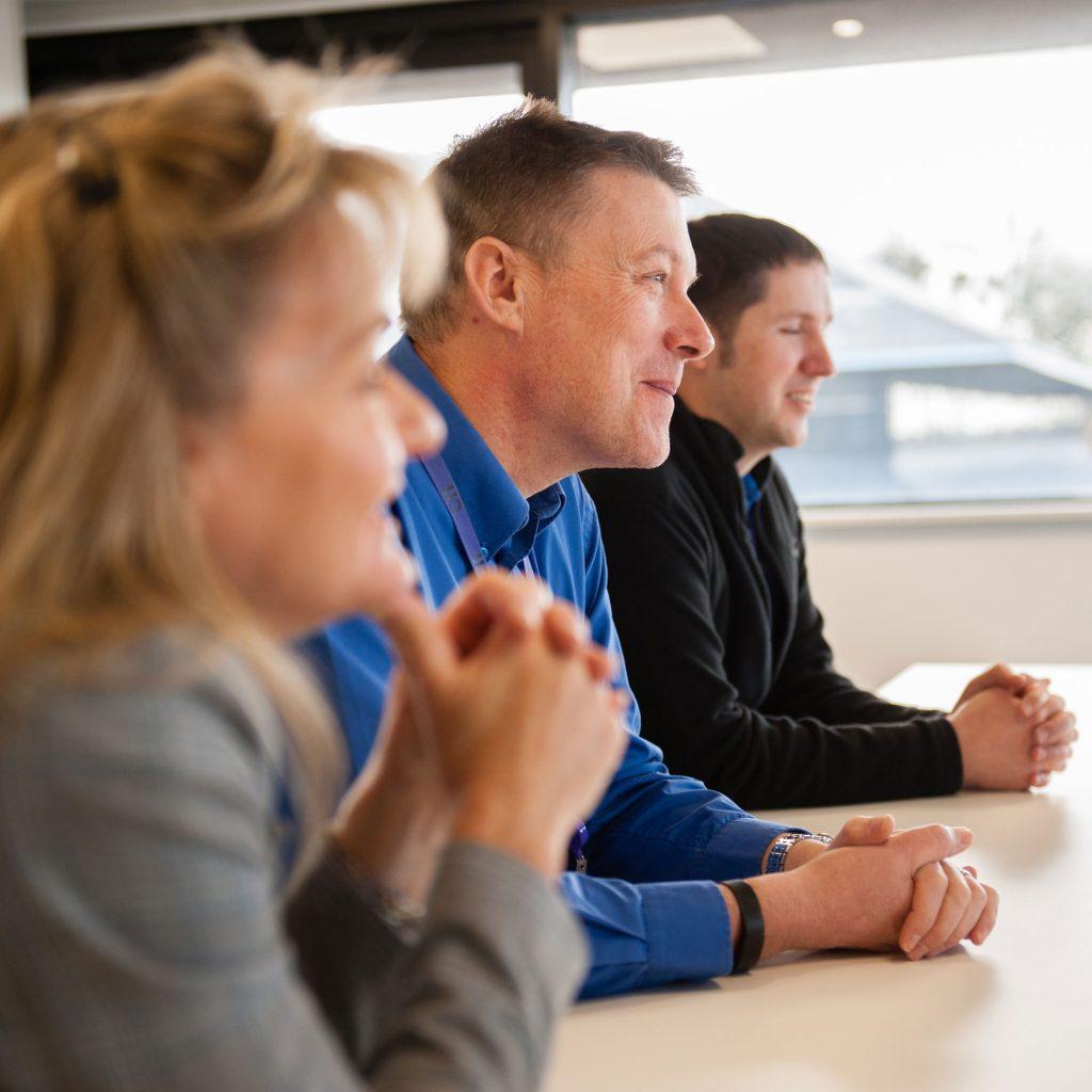 Close up of three people sat at table smiling at C11