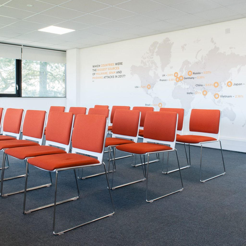 Rows of orange chairs in empty room at C11