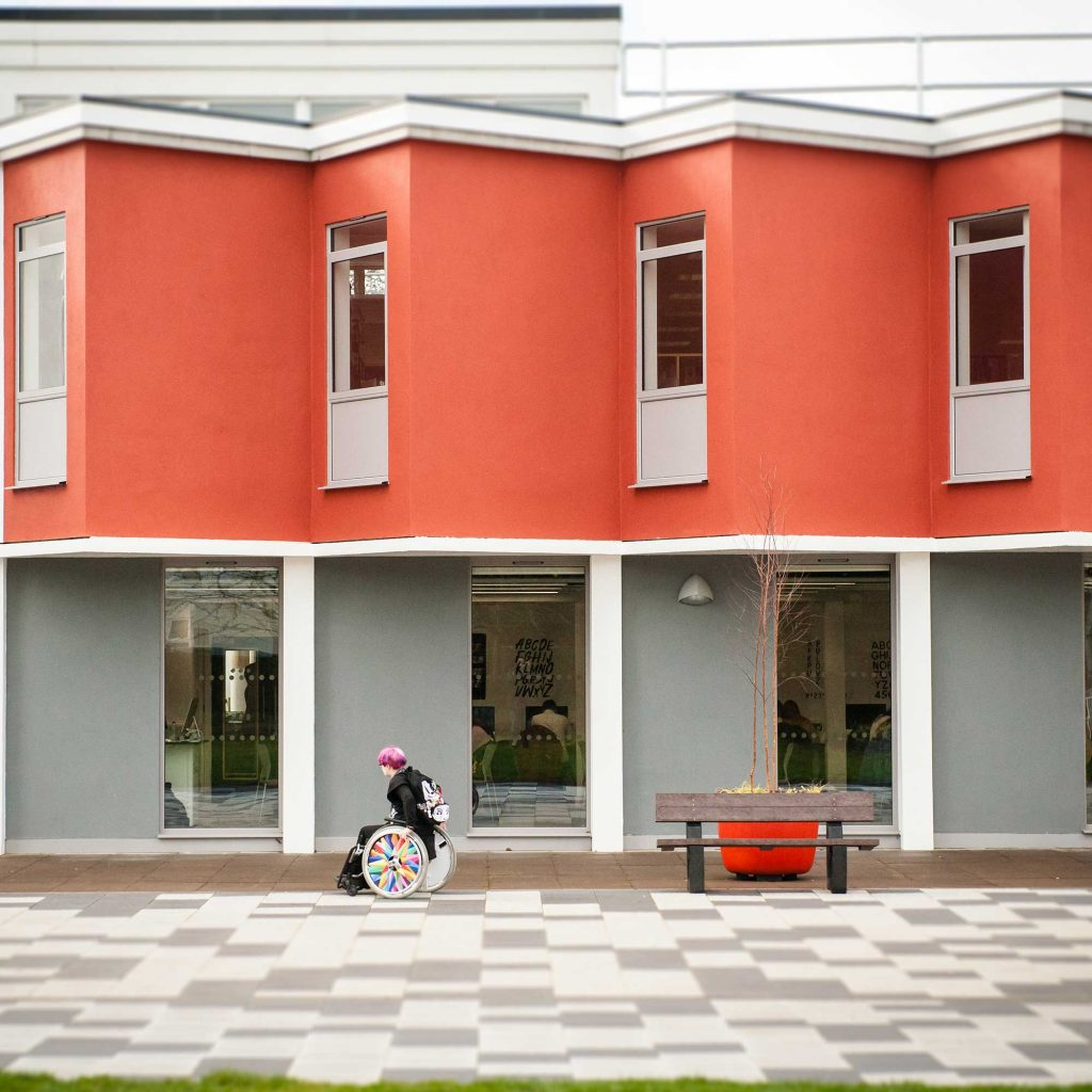 Student in wheelchair going past Design Studios at Park Campus