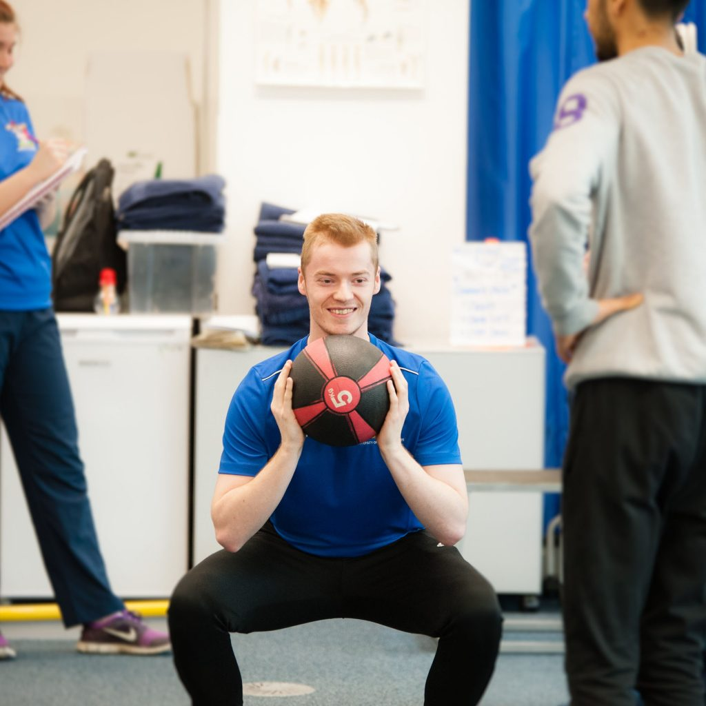 A student on the Sports Therapy MSc course doing squats whilst holding a 5kg powerball