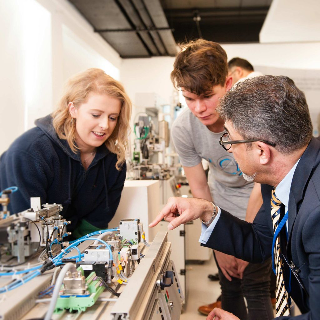 Lecturer showing students some engineering equipment