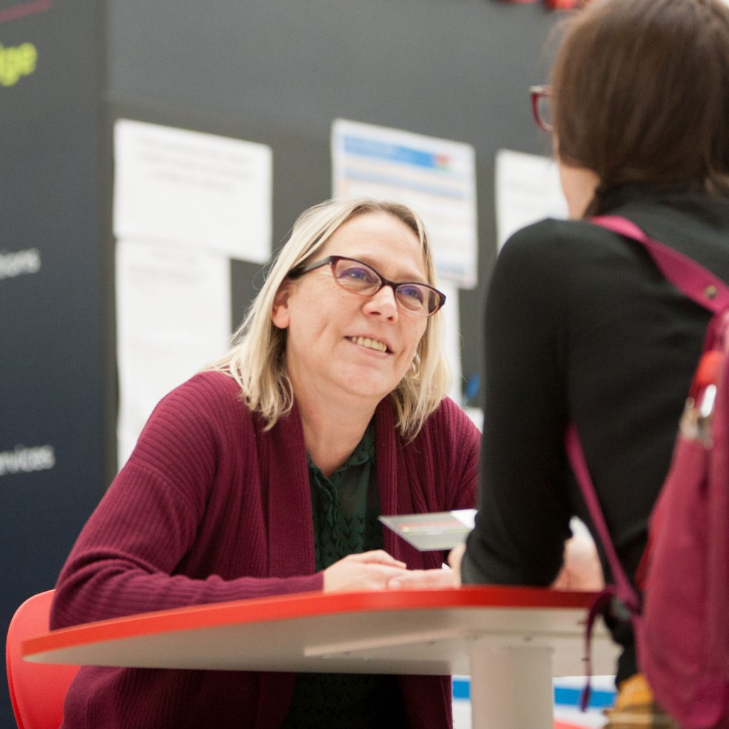 Helpzone advisor talking to student, smiling