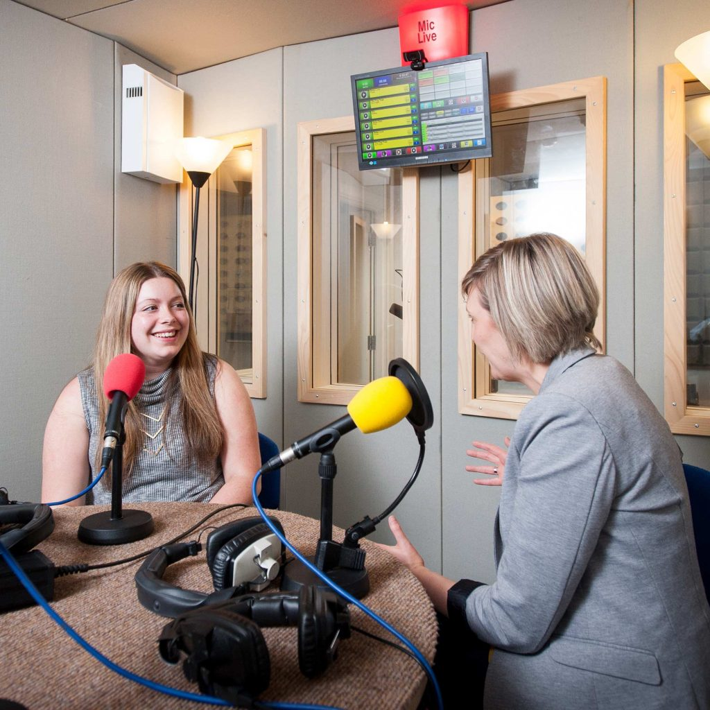 Student and radio presenter chatting on air in the radio room