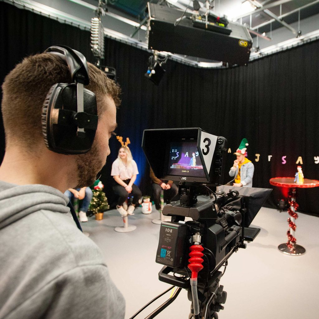Student operating a camera in the TV studio