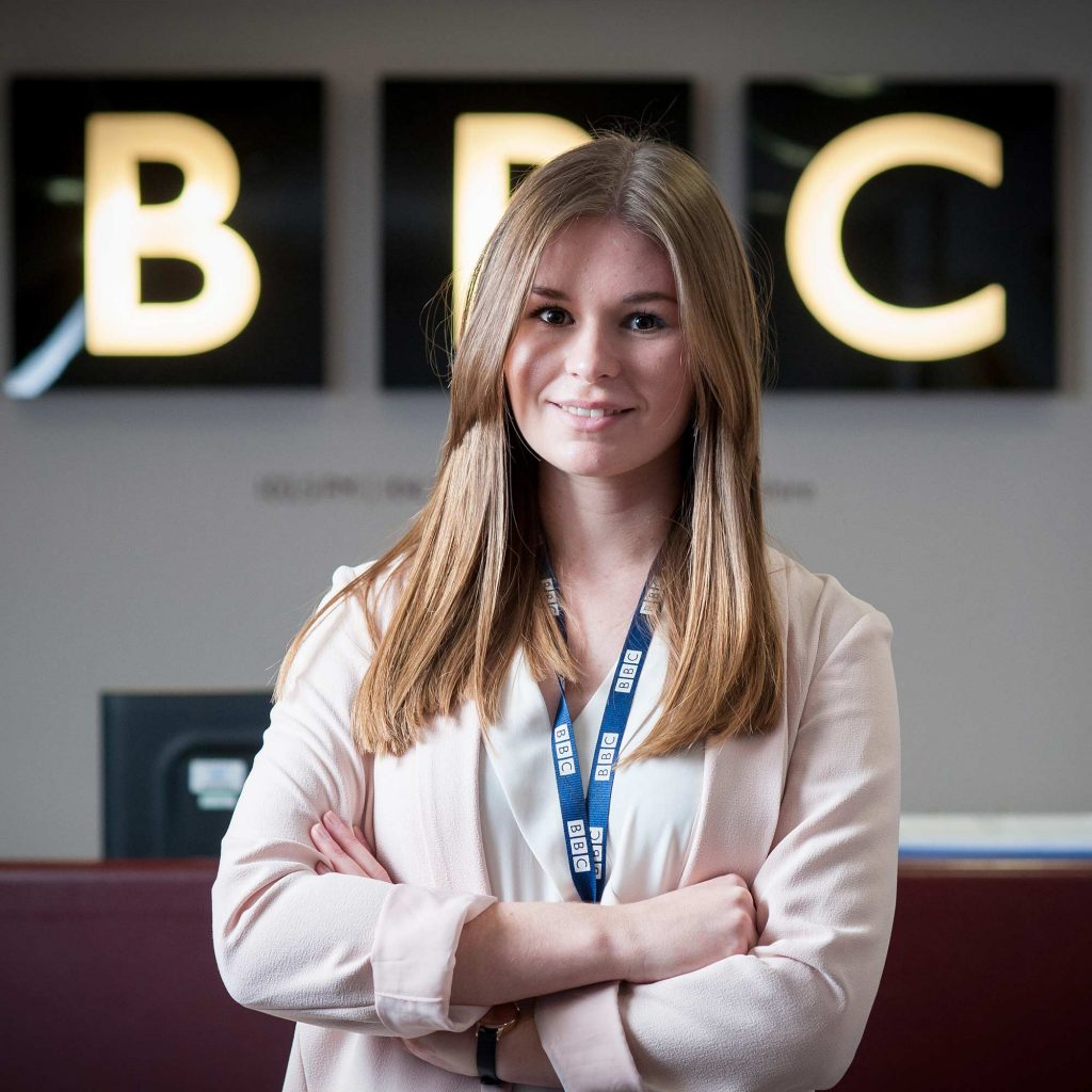 Graduate smiling infront of BBC sign