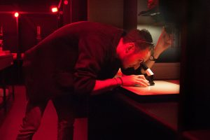A man looking through a magnifying glass in a darkroom with redlight