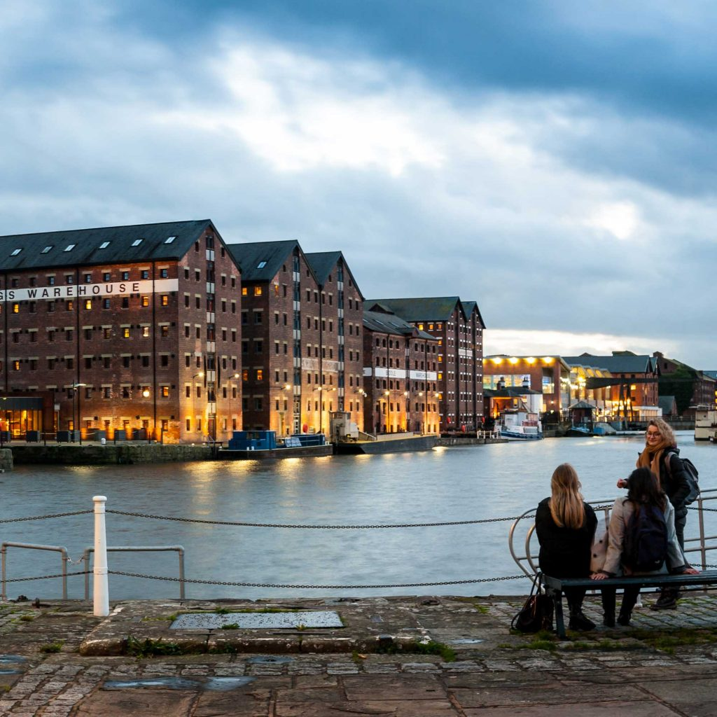 Students sitting on a bench in front of water at Gloucester docks