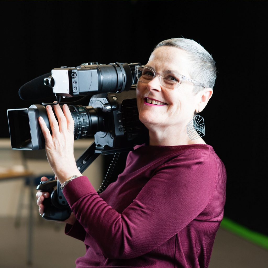Fiona Curran, Lecturer in Media, smiling holding camera