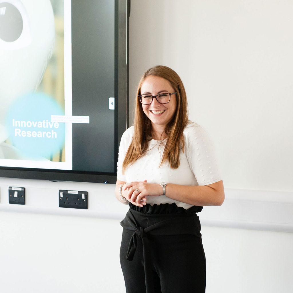 Member of staff smiling delivering presentation