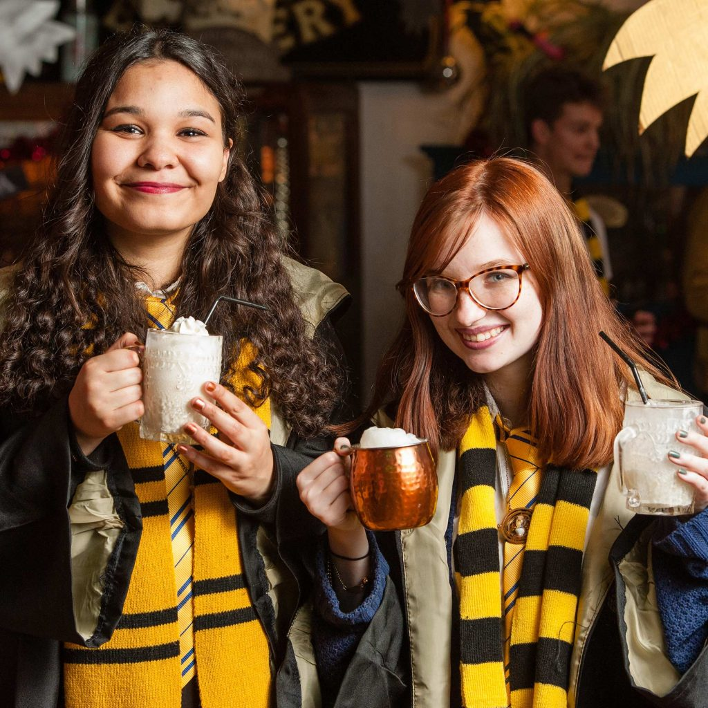 Students dressed up in harry potter costumes drinking butter beer