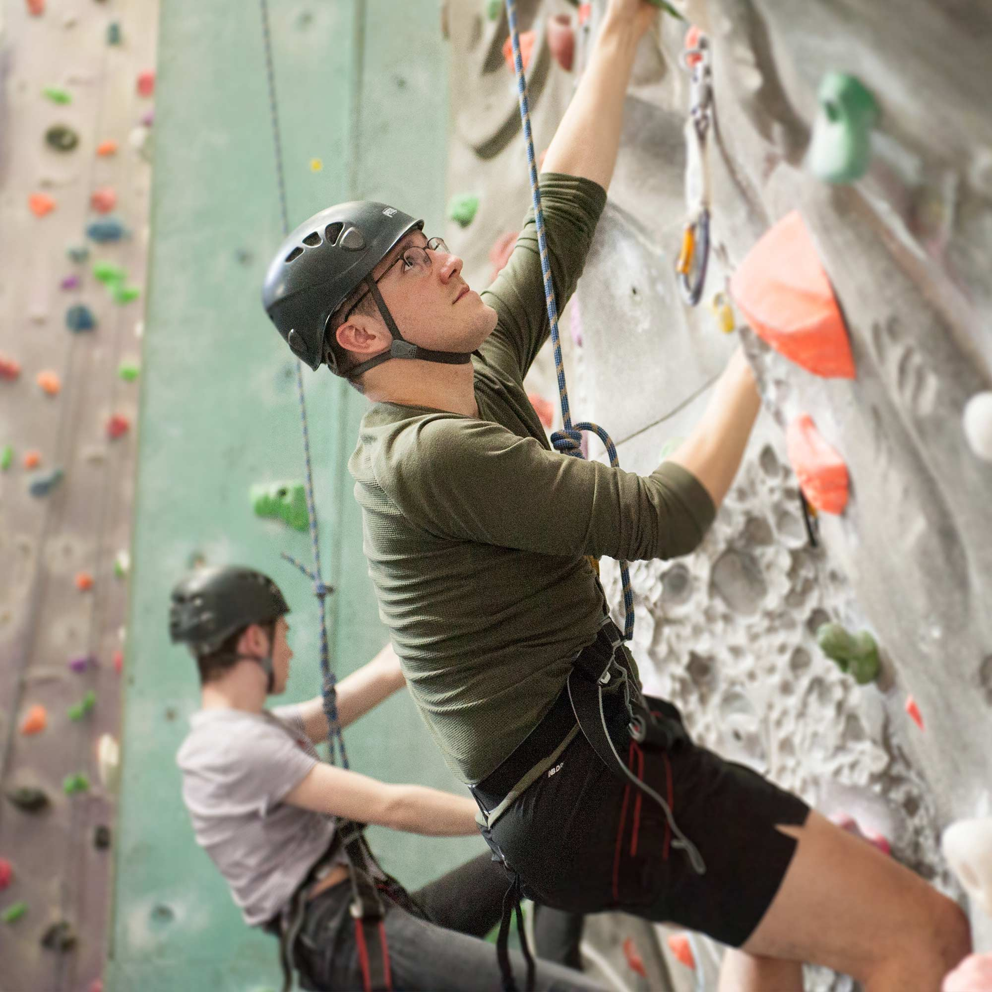 Student using an indoor climbing wall