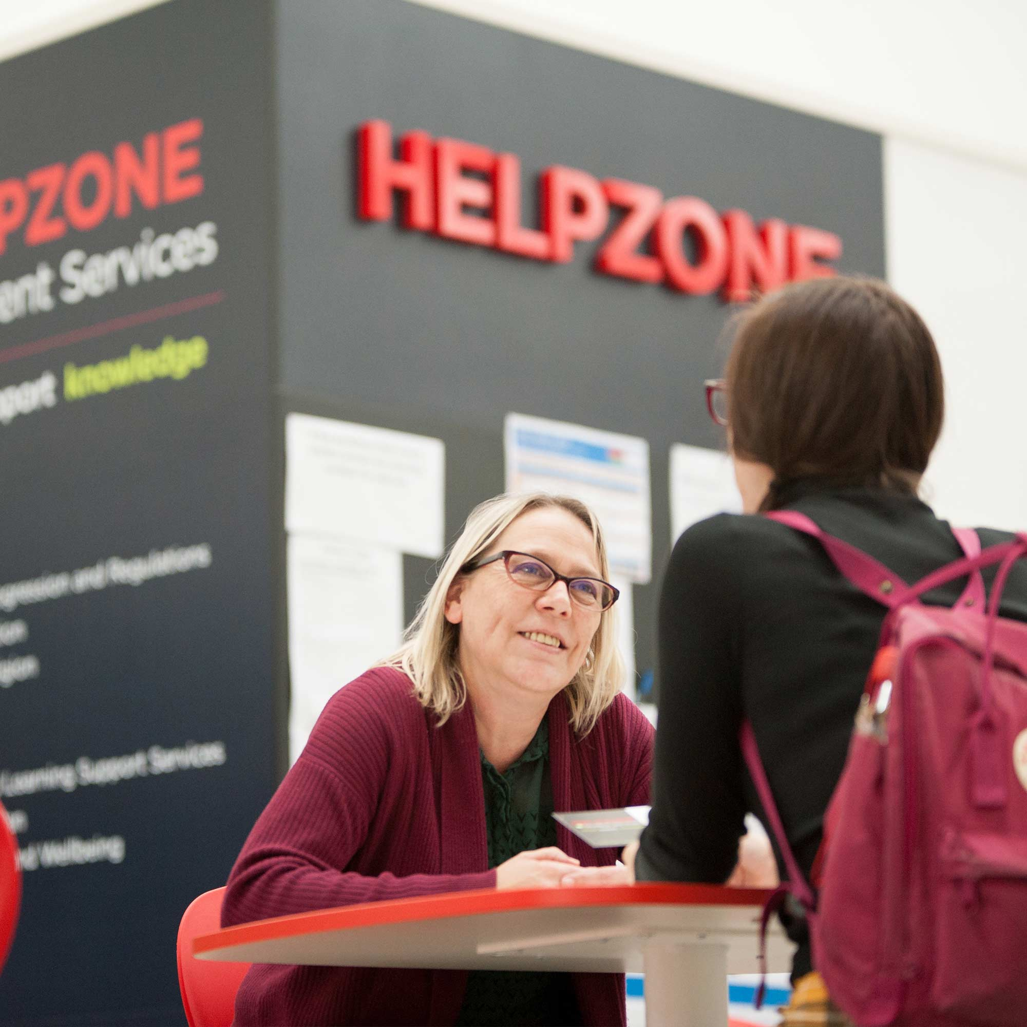 Student talking to an advisor at the Help Zone