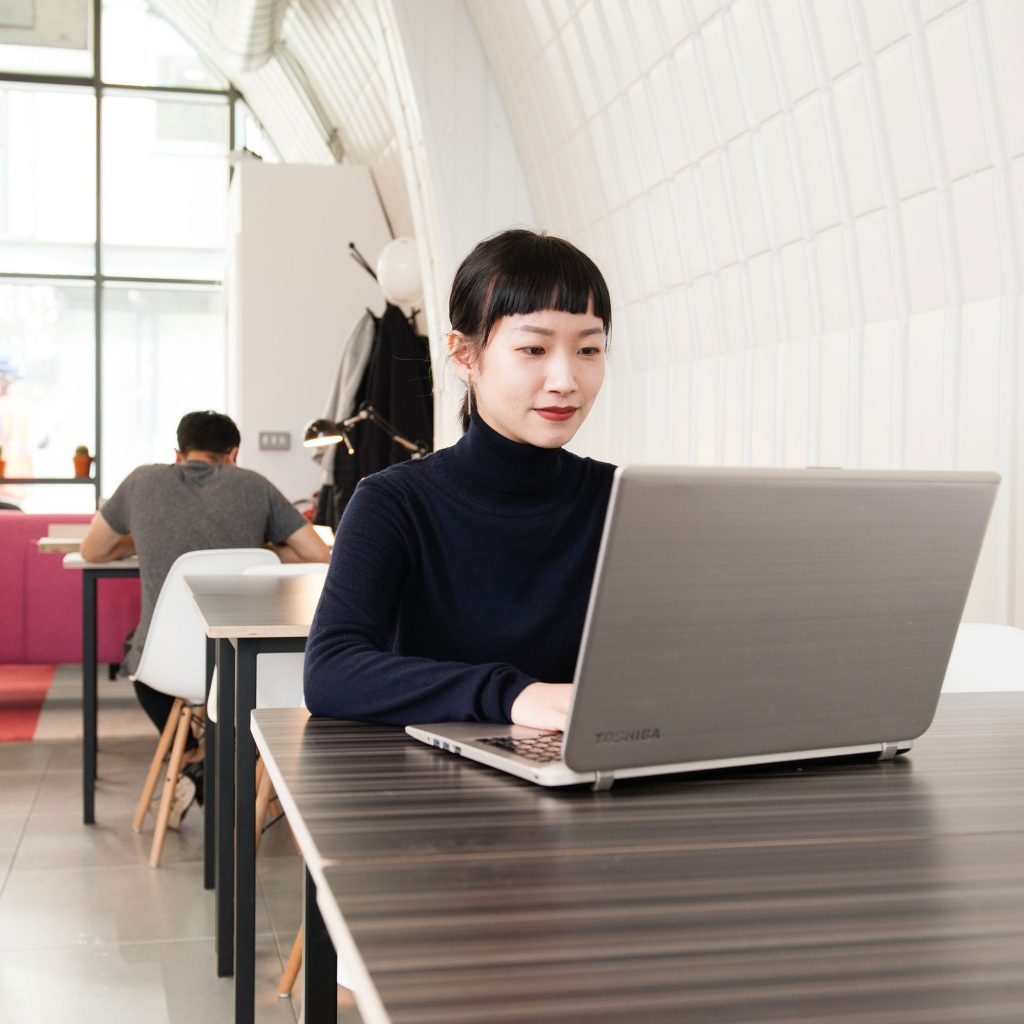 International student sitting at a desk and using a laptop