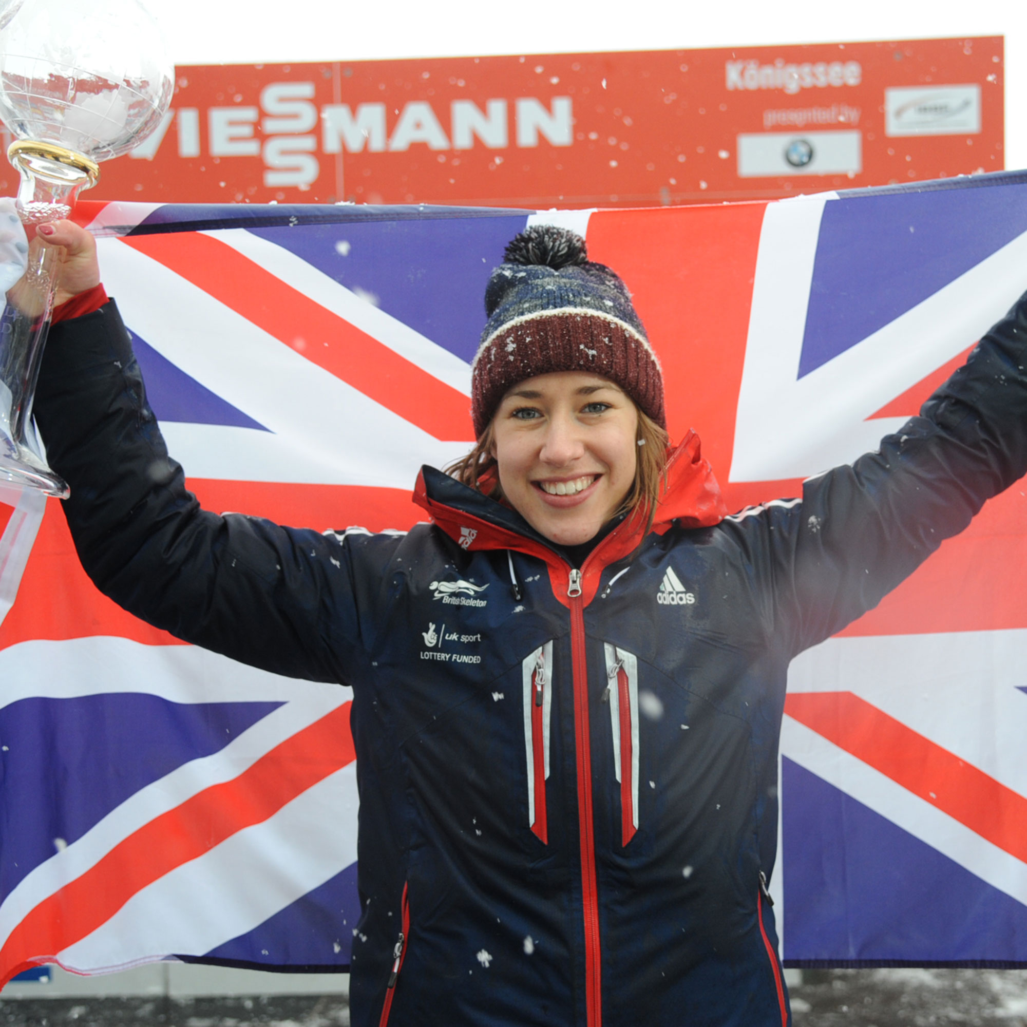 Lizzy Yarnold holding flag and trophy