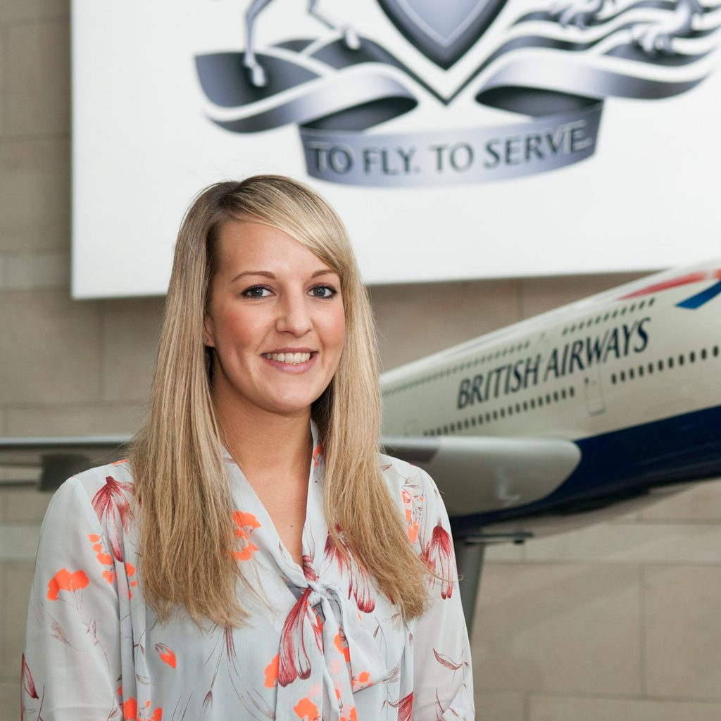 Graduate standing in front of a British Airways model plane