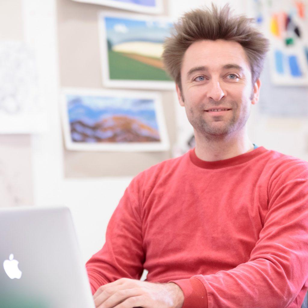Lecturer in art studio working on a MacBook