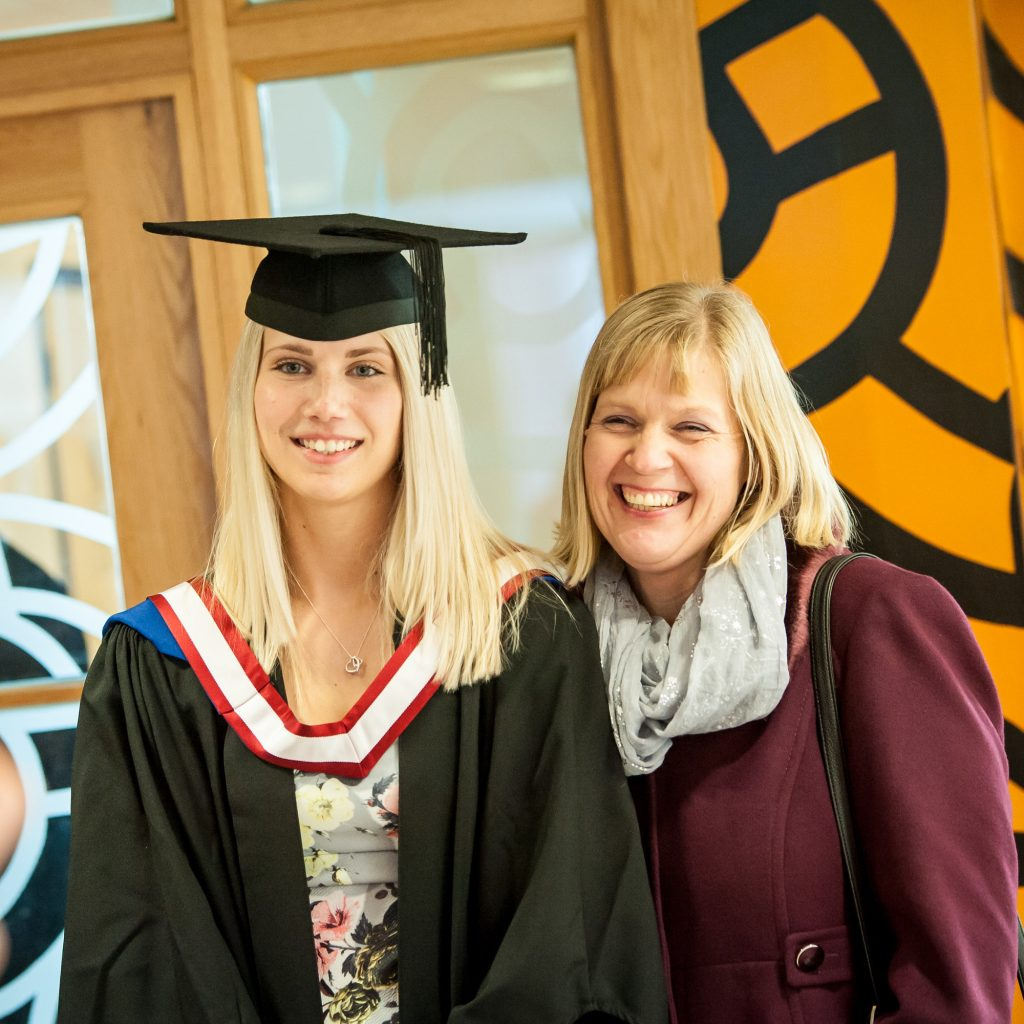 Happy graduate being photographed with her smiling mother