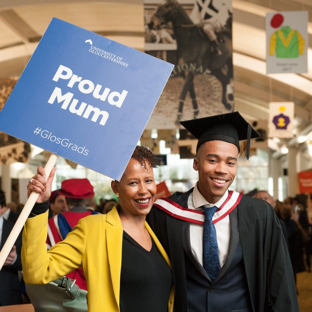 Graduate with his mother holding up a Proud Mum sign