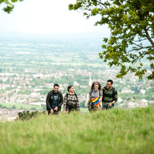 Students walking up a hill in Cheltenham countrysid