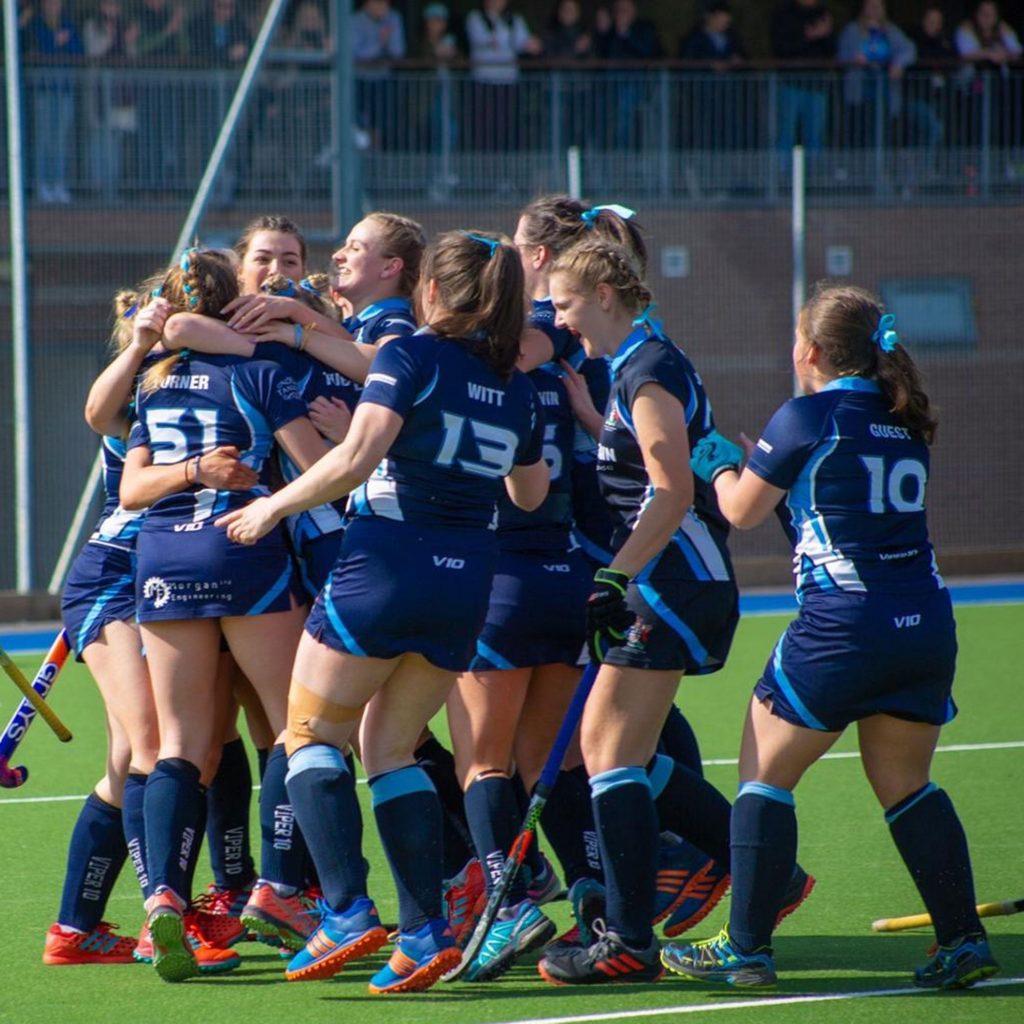 Female hockey team celebrating a goal