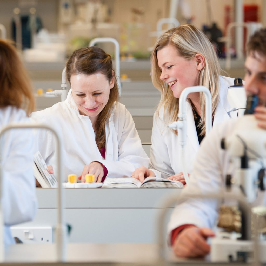 Two students in lab smiling