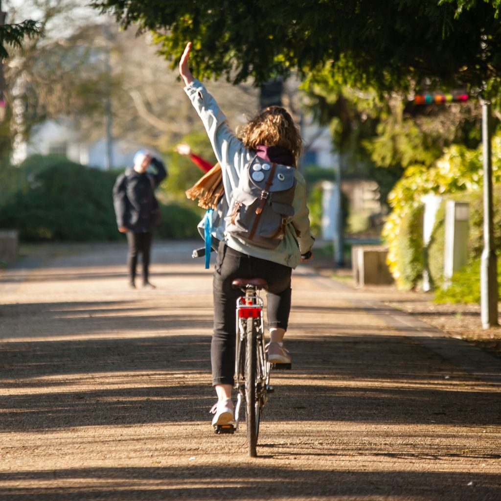 Woman on a bicycle waving
