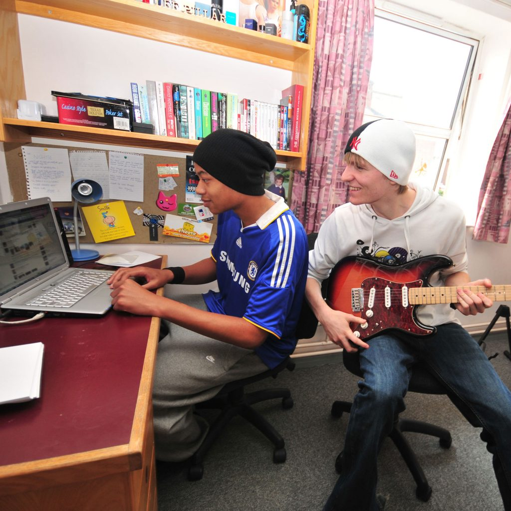 Two students with guitar looking at computer in Hardwick halls of residence