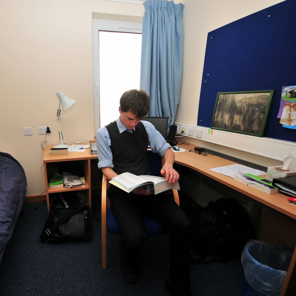 Student sat at desk reading book in Ermin Hall halls of residence