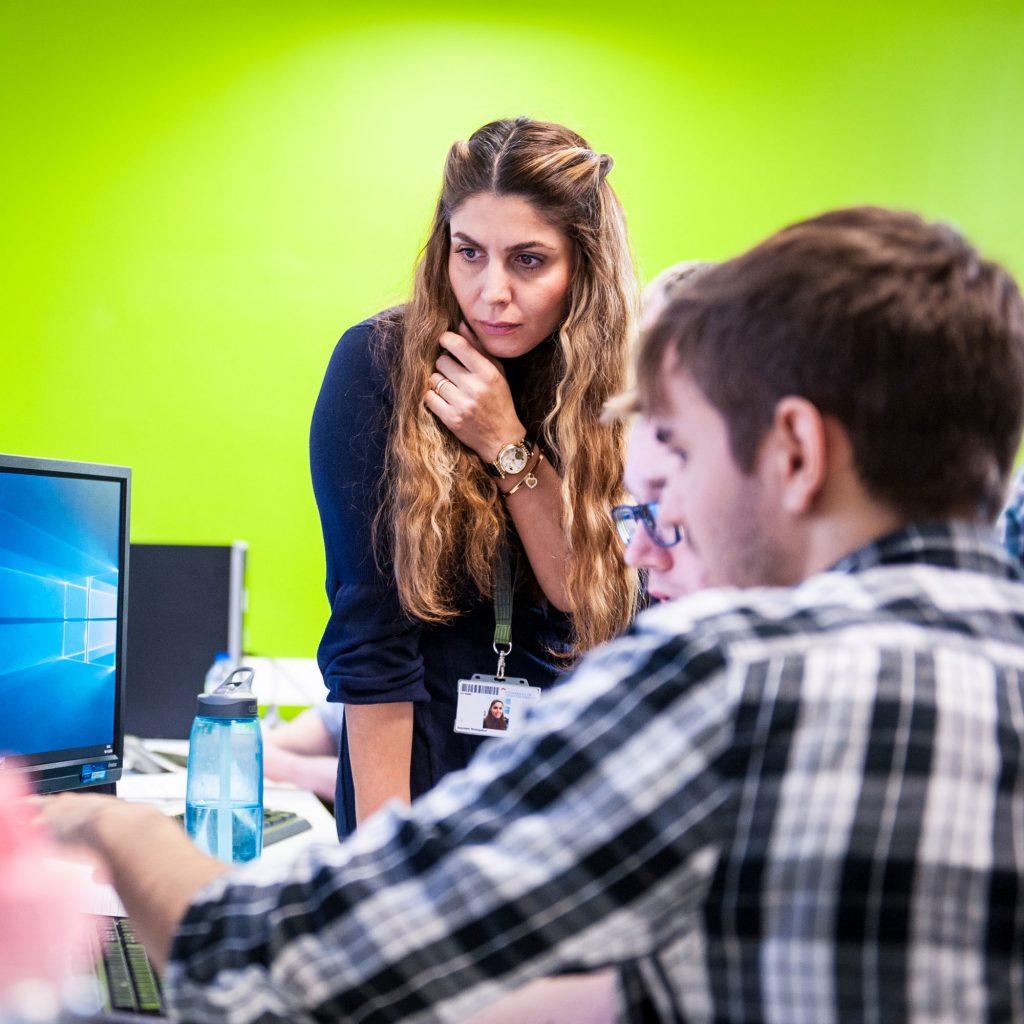 Data scientists gathered around computer