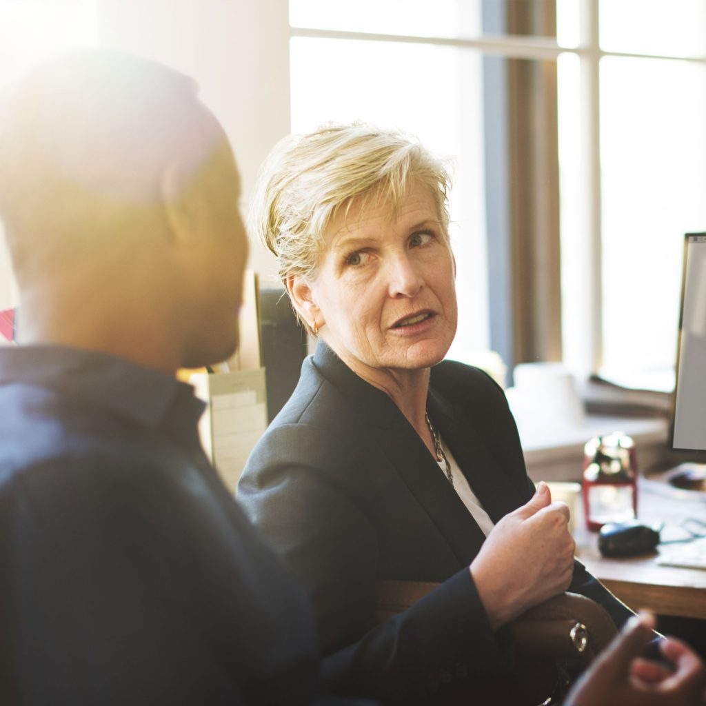 Woman in business attire sat at desk talking to man
